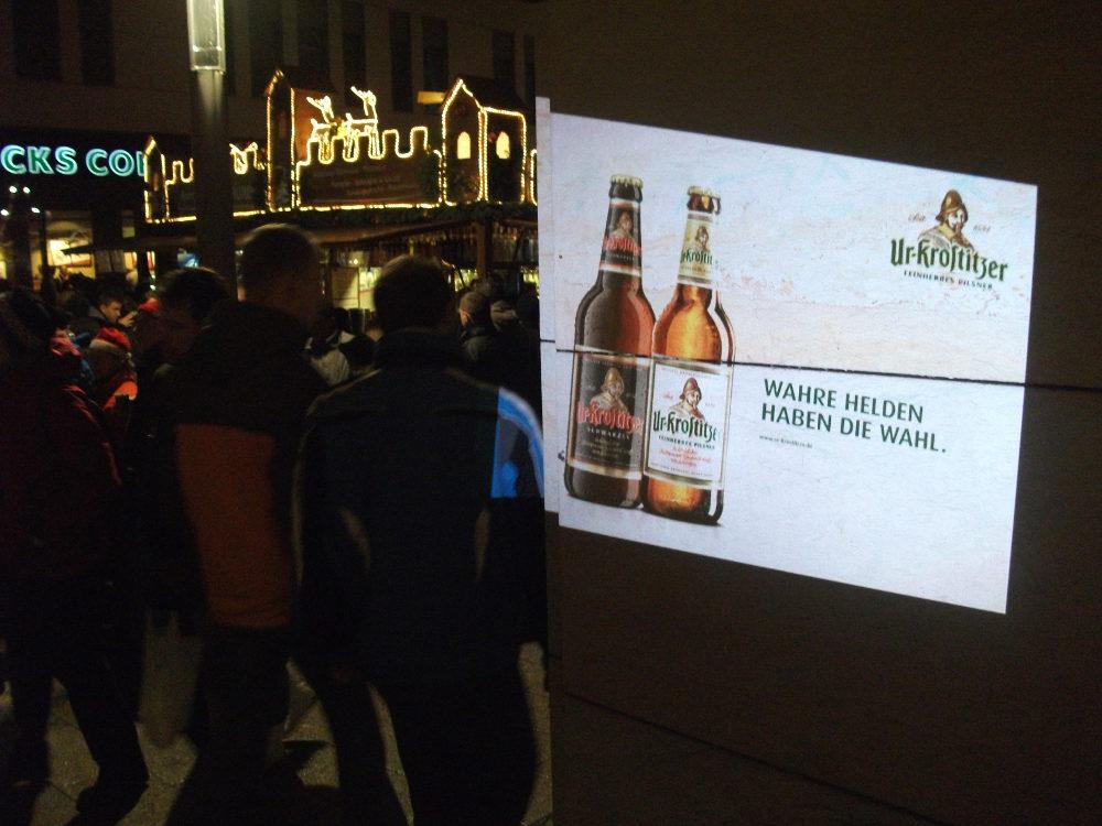 Mobile Projektion-Werbung - BeamerMan-Lichtprojektion mit Handbeamer auf dem Weihnachtsmarkt