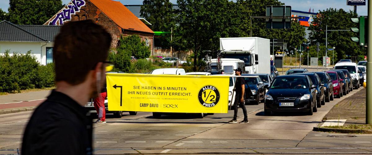 Tragbares Werbebanner zeigt Autofahrern den Weg zum Flagship Store