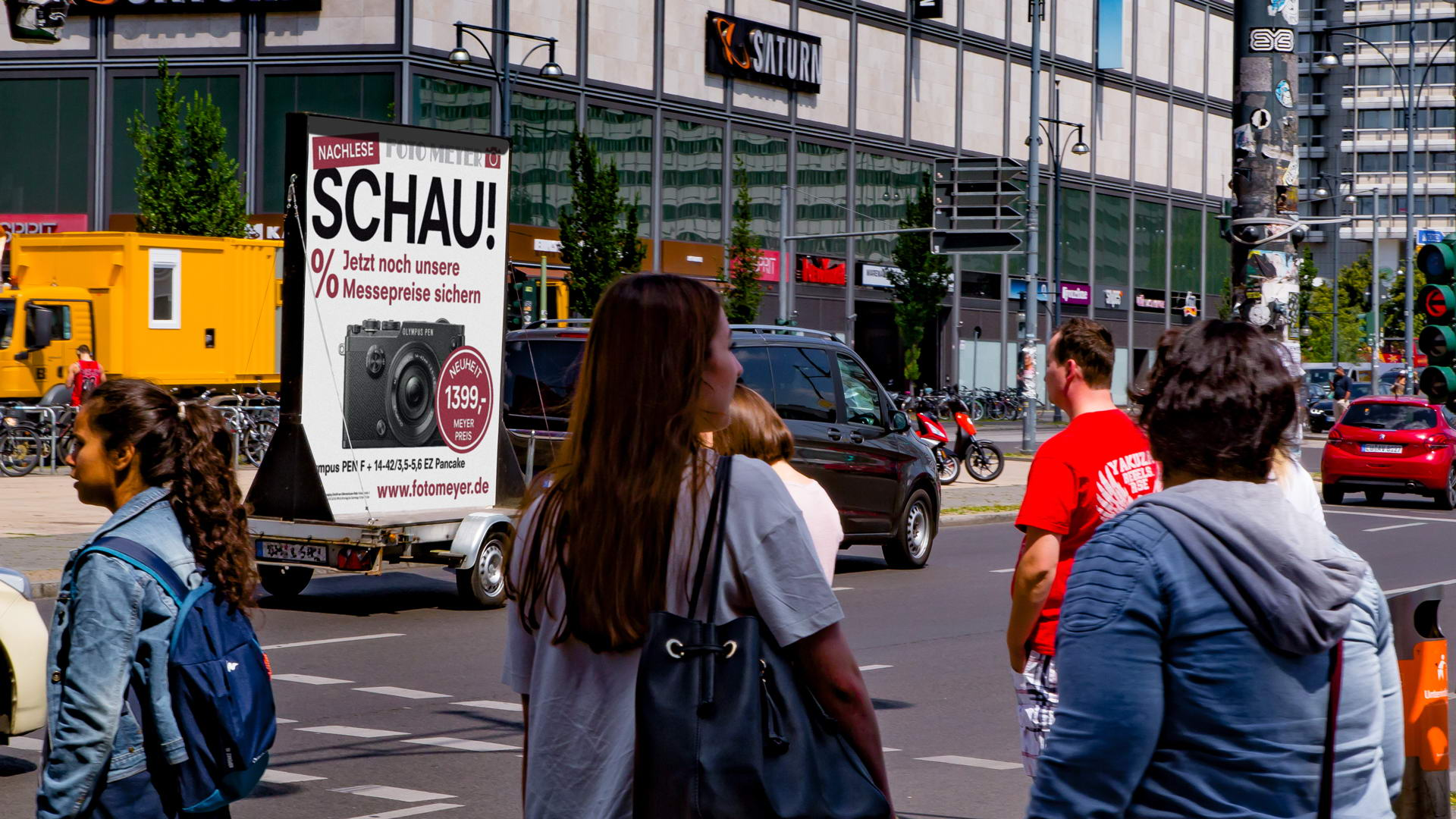 Werbeanhänger mit Plakaten wird von einem Auto über eine Kreuzung gezogen