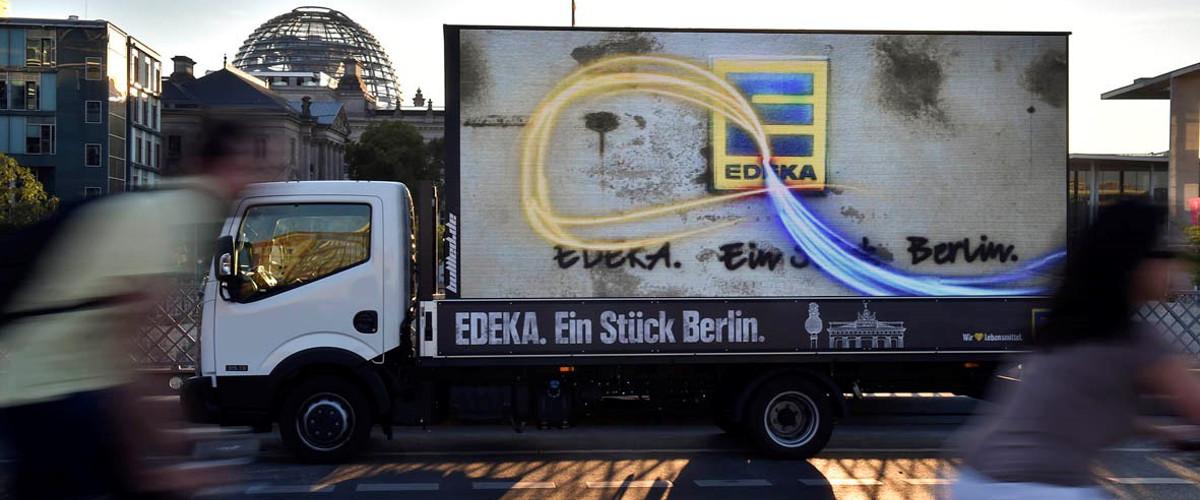 Lkw-Werbung mit LED Würfel an einer Straße