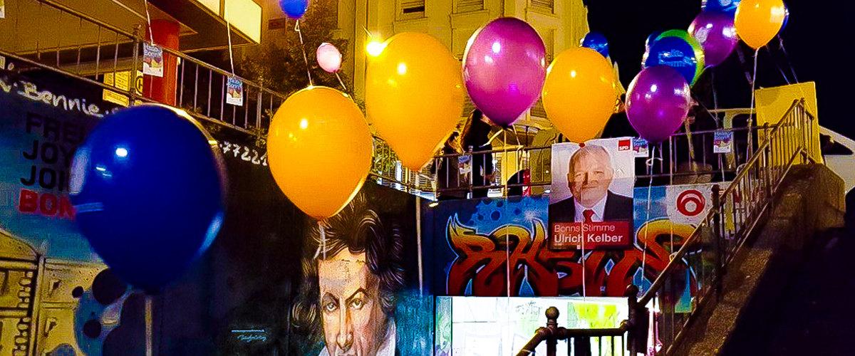 Bunte Guerilla Ballons festgebunden am Geländer