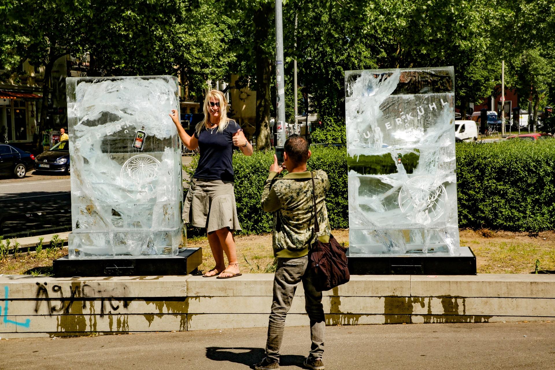 Frau steht vor Jägermeister Eisplakaten und ein Mann fotografiert sie