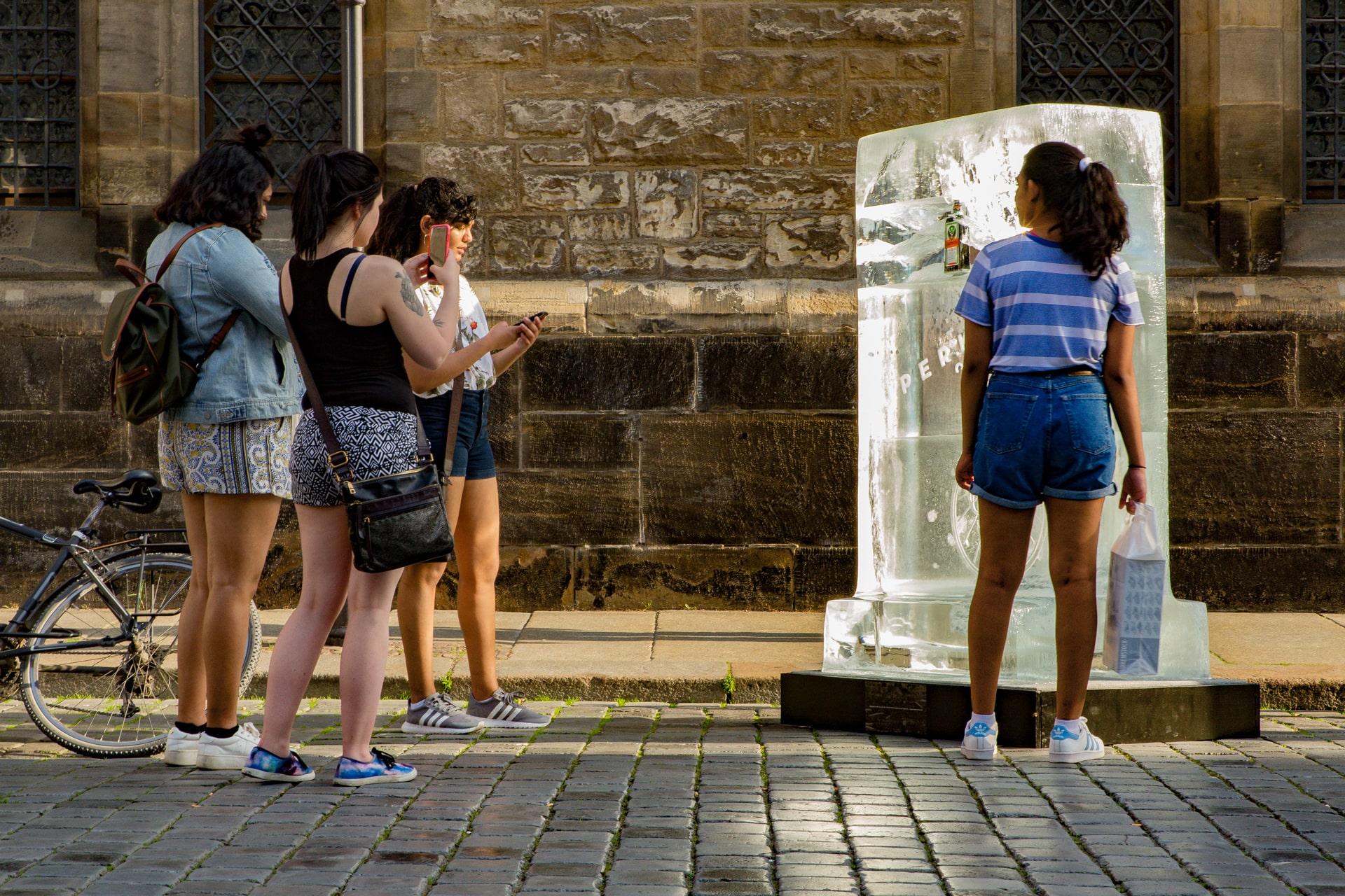 Männergruppe schaut auf Eisplakat - ein Mann umarmt den Eisblock