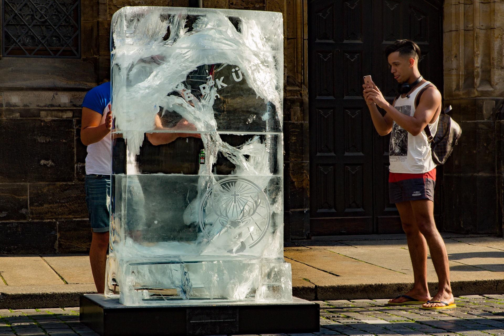 Ein Mann berührt Eisblock und ein anderer Mann fotografiert das Eis-Plakat von Jägermeister
