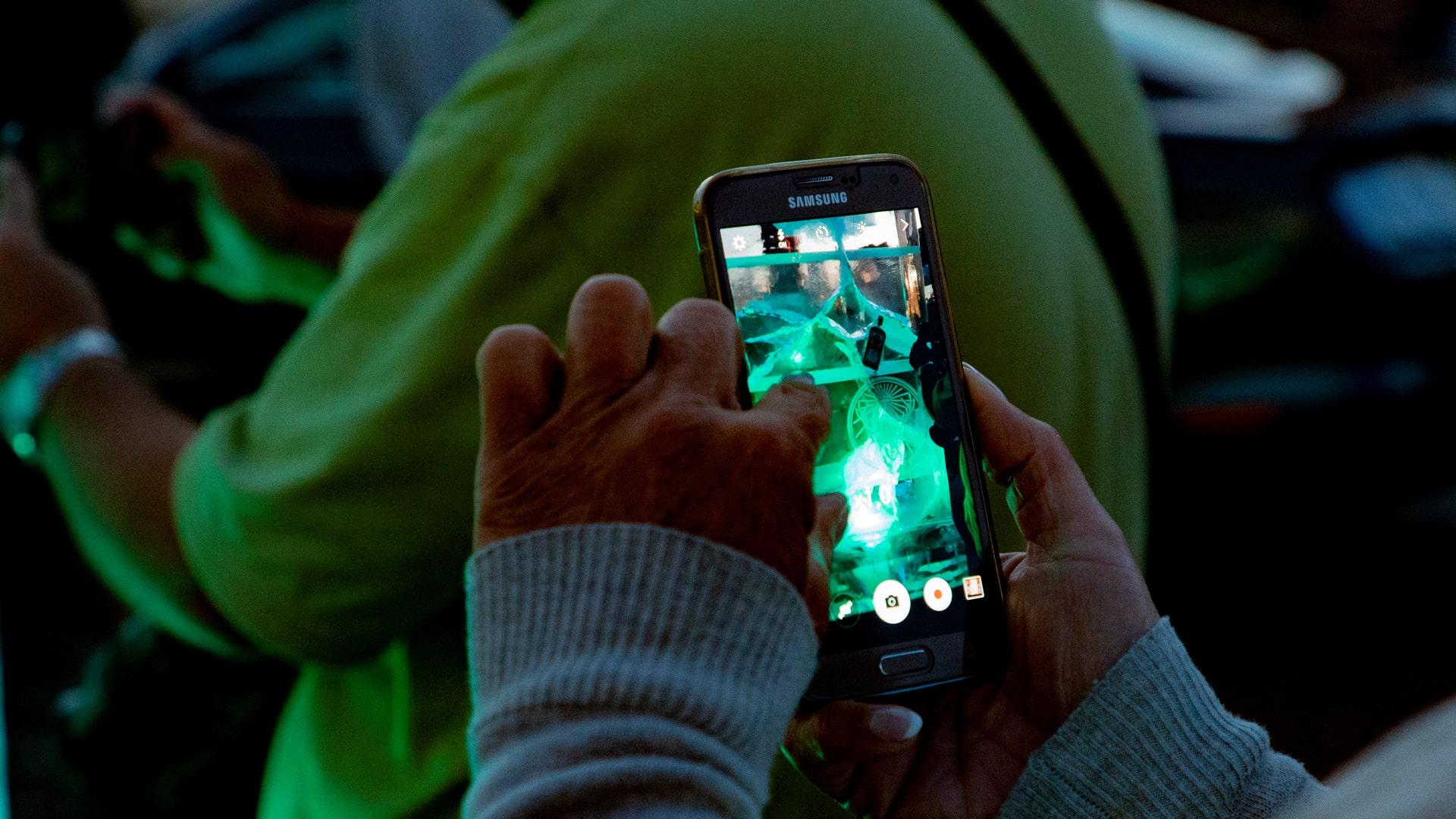 Passantin fotografiert grün beleuchtete Eisplakate von Jägermeister mit Smartphone