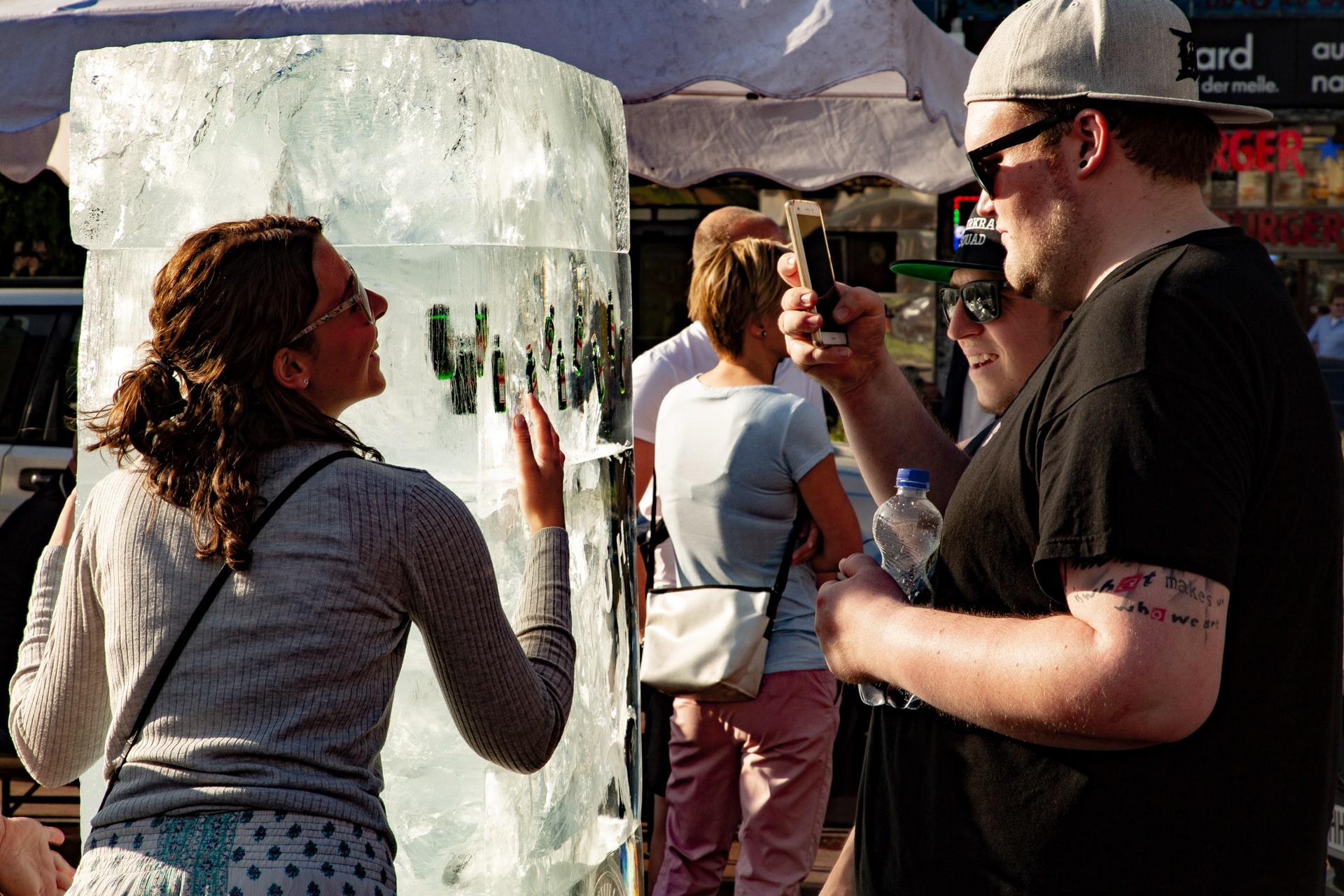 Passantin umarmt Jägermeister Eisplakat und wird dabei fotografiert