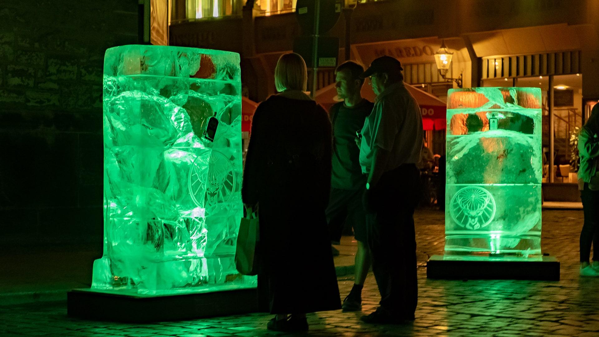 Zielgruppe schaut auf neongrün illuminierte Eisblock-Plakate von Jägermeister