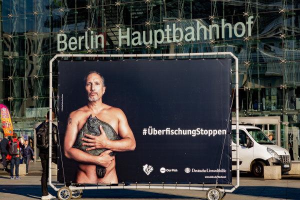 Bennu Fürmann zeigt sich nur mit einem Fischbedeckt auf einem Banner - Überfischung stoppen