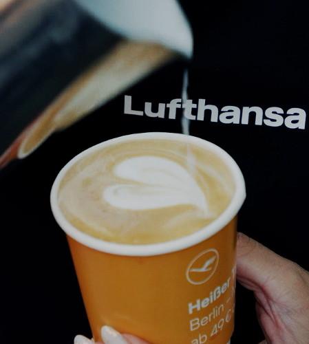Barista formt Herz im Kaffeebecher