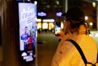 Passantin fotografiert den CLP-Mover mit Plakatwerbung von The Umbrella Academy