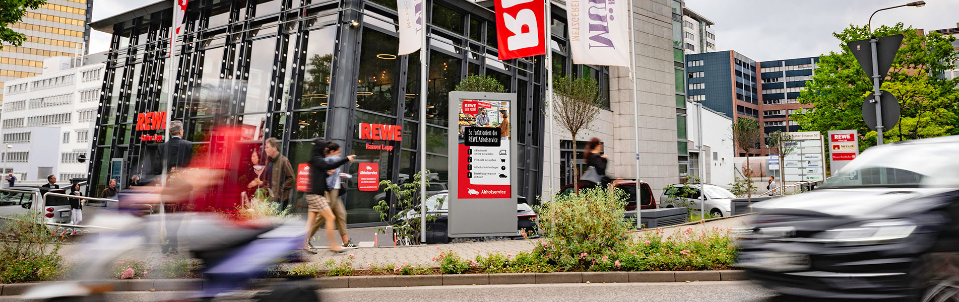 Digitales City Light Poster vor einem lokalen Rewe
