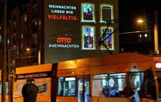 Straßenbahn vor Hauswand mit digitelem Riesenposter